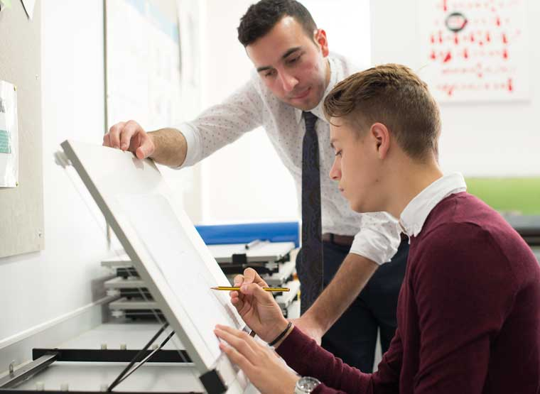 Sixth Former and teacher at drawing board